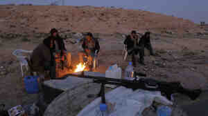 Libyan anti-government fighters sit by a fire to stay warm as they control a checkpoint on the outskirts of the southwestern town of Nalut, Libya,  Monday. The town is currently in control of the Libyan anti-government forces.