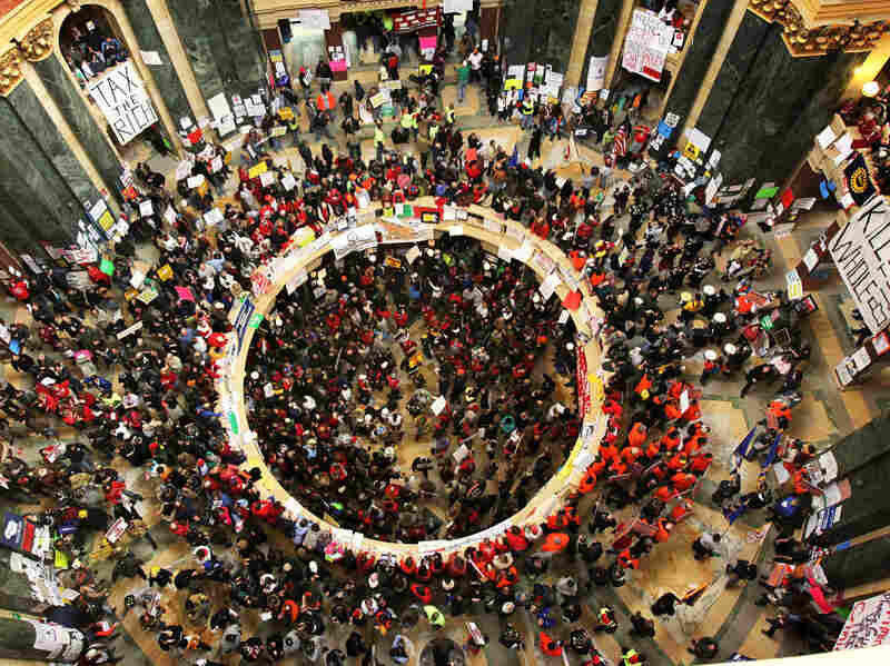 Protesters demonstrating in the capitol rotunda last week in Madison, Wisconsin, protesting the governor's attempt to push through a bill that would restrict collective bargaining for most government workers. Early Friday morning the state assembly passed the bill.