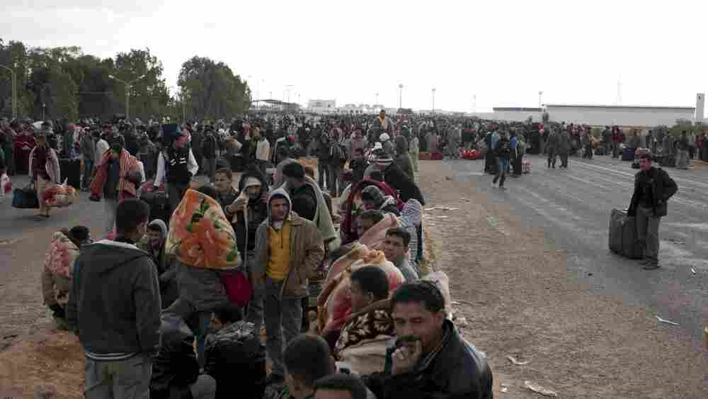 Egyptians wait to take buses after fleeing from Libya, on February 27, 2011, near the Tunisian city of Ben Guerdane.