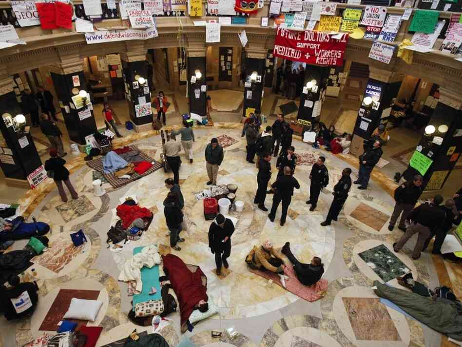 Police and demonstrators in the Wisconsin Capitol rotunda on day 14 of protests, Monday, Feb. 28, 2011.
