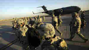 Members of the U.S. Army's 1st Brigade, 3rd Infantry Division, based at Fort Stewart, Ga., walk toward a C-17 aircraft at Sather Air Base in Baghdad on Nov. 30, beginning their journey home after a year in Iraq.