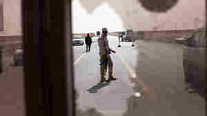 A volunteer soldier waves cars through a checkpoint in Ajdabiya on Tuesday.