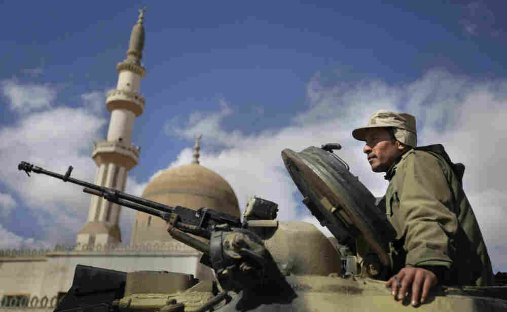 A pro-Gadhafi Libyan soldier sits in an armored vehicle next to a mosque in Qasr Banashir, southeast of Tripoli, on Tuesday.