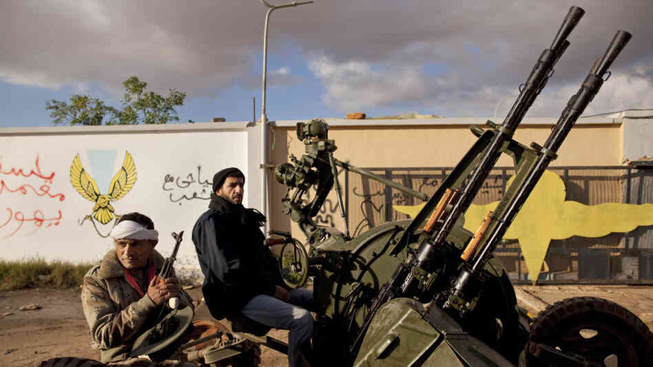 Rebel Libyan fighters sit on an anti-aircraft battery outside a military base in Benghazi, eastern Libya, Monday, Feb. 28, 2011.