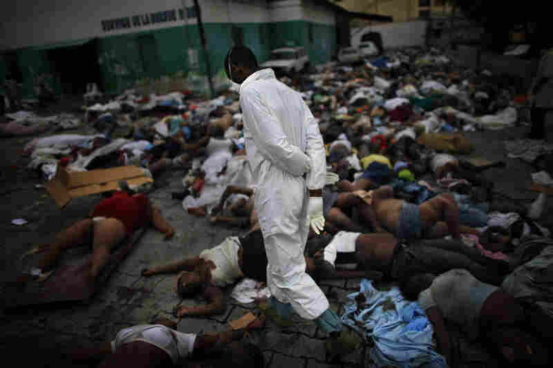 Morgue workers walk among the thousands of bodies piled up at the National Hospital in downtown Port-au-Prince. The earthquake left the Haitian capital almost totally destroyed, killing hundreds of thousands and overwhelming the morgue facilities with victims.
