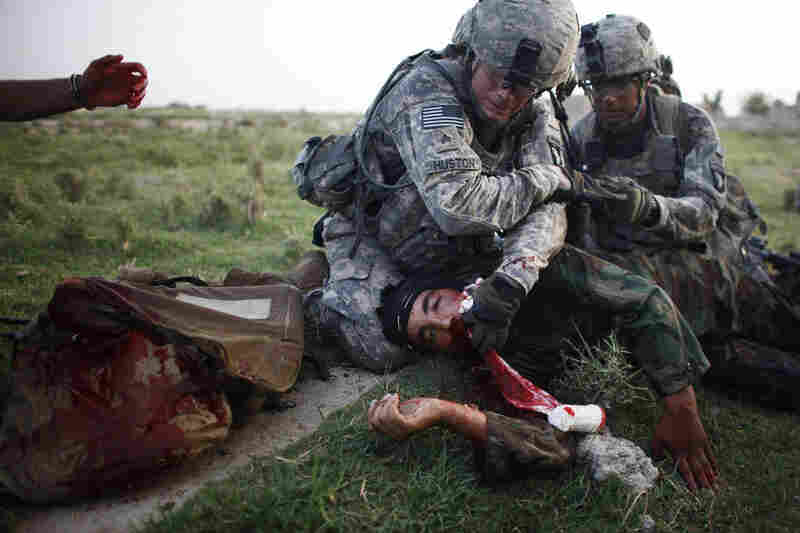 Medic Paul Huston and Staff Sgt. Jaime Newman, of the 101st Airborne Division, work frantically to save Atiqullah Obaidullah, an Afghan National Army counterpart, who was shot in the head just seconds before by an insurgent sniper. American forces work closely with their Afghan counterparts and treat them as equal partners in the fight to secure the country.