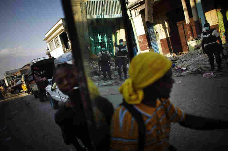 Looters carry away a stolen mirror, which shows the reflection of local police standing on the streets in downtown Port-au-Prince, Haiti. Looting and violence raged in the commercial district of the Haitian capital after the devastating Jan.12., 2010, earthquake. In many cases, the police gave up on chasing people out of the area.
