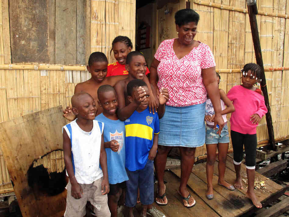 Fifty-year-old Segunda Ayobi, with her extended  family. Ayobi, who lives in a slum in Guayaquil, Ecuador, enrolled her son Mario in a  shelter when he began to miss school, to keep him away f