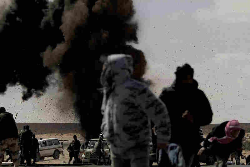 Rebel fighters run for cover as an air force jet drops a bomb on the outskirts of the oil-rich town of Ras Lanuf on Tuesday.
