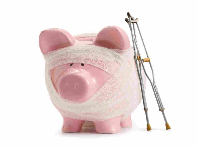 Bandaged piggy bank with crutches.