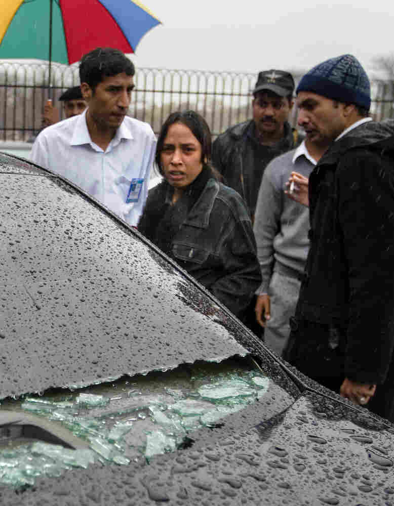 A relative of Shahbaz Bhatti looks at his damaged car at a hospital in Islamabad.