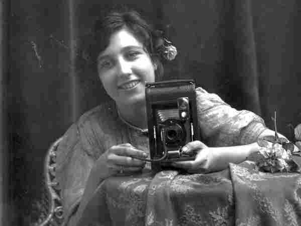 A young, unknown woman holds a camera, circa 1885-1910