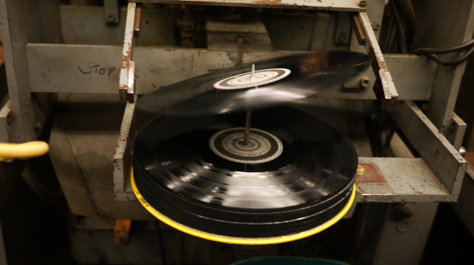 A 12-inch record tips onto the spindle at EKS Manufacturing. (Jacob Ganz)