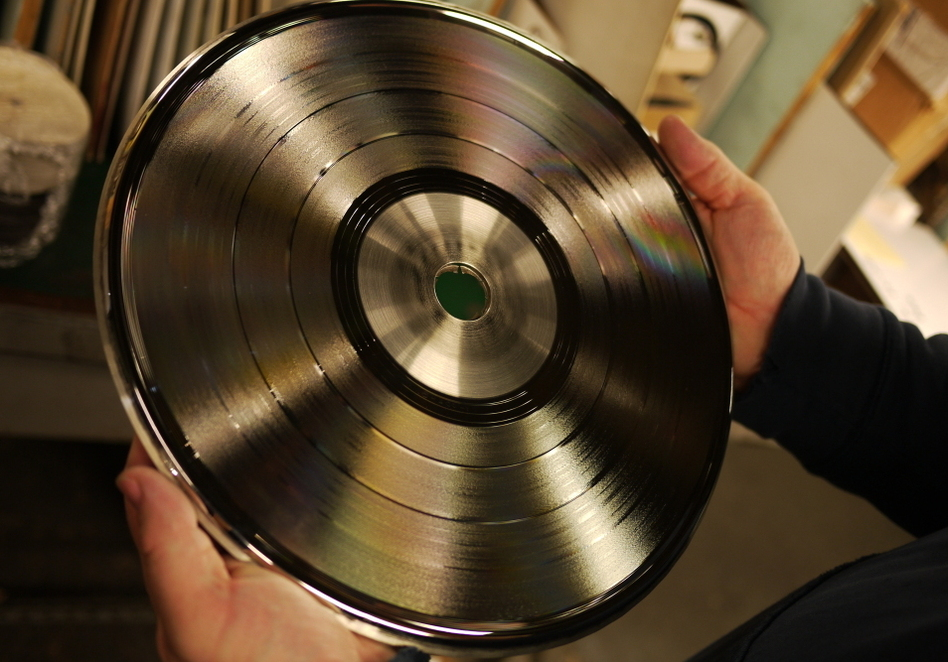 EKS owner Will Socolov holds a stamper — half of a pair of nickel plated discs with a spiral ridge to press a groove into one side of soft vinyl. (Jacob Ganz)
