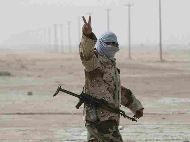 """A Libyan rebel soldier flashes the """"V for victory"""" sign as he prepares for battle in the eastern city of Ajdabiya on Wednesday."""
