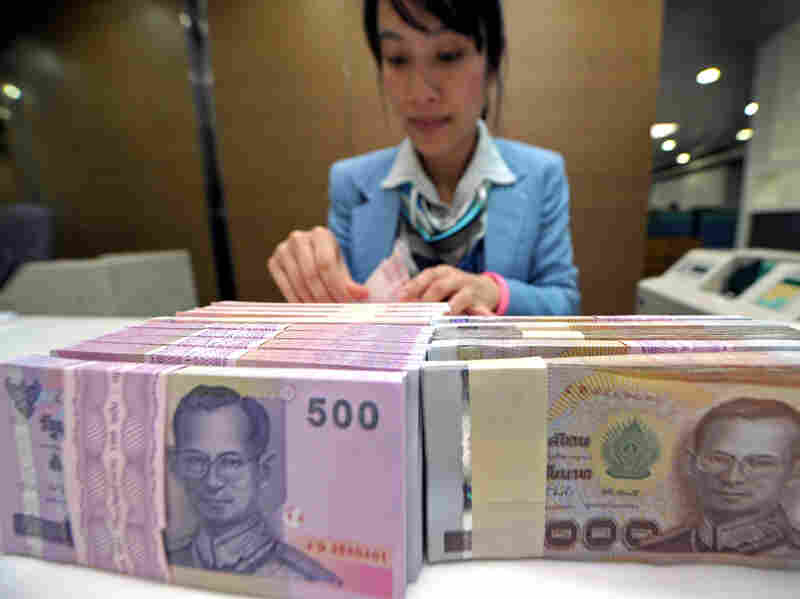 An employee counts bundles of Thai bahts at Krung Thai Bank in Bangkok in October. A tidal wave of money is pouring into Asia and driving up regional currencies.
