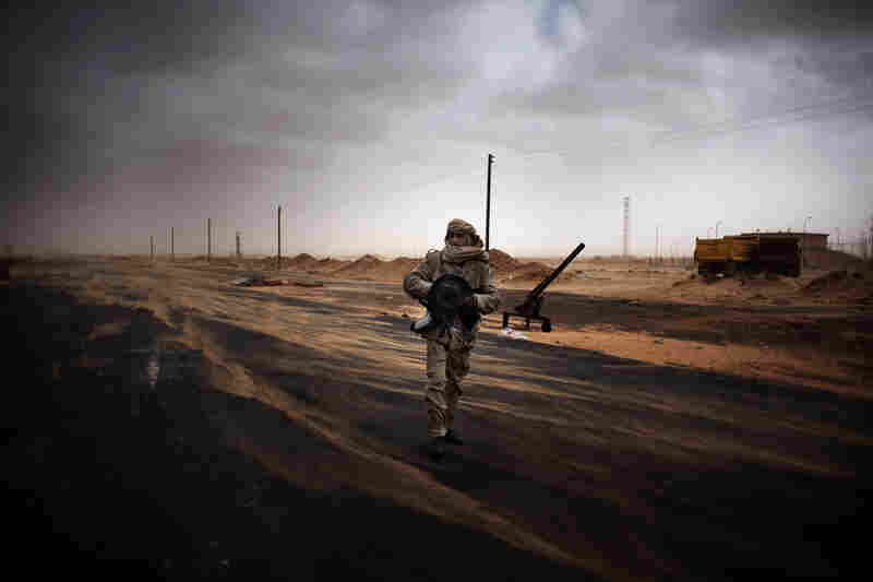 A rebel fighter stands at a checkpoint Saturday in Ras Lanuf, where up to 10 people were killed and more than 20 wounded in clashes between opposition forces and Gadhafi loyalists.