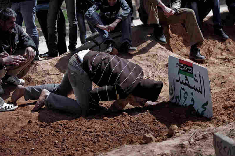 A mourner kneels over the grave of a relative recently killed in a battle between rebel fighters and forces loyal to Libyan leader Moammar Gadhafi for control over the town of Bin Jawad, Libya, on Monday.