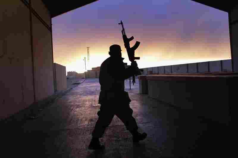 A Libyan border guard walks through an empty customs hall on the Libya-Egypt border on Thursday.