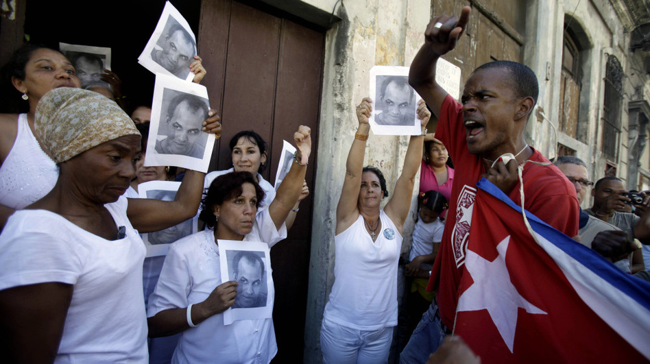 A government supporter (right) chants as members of the dissident group Ladies in White hold up images of Orlando Zapata Tamayo, a prisoner who died of a hunger strike, on the anniversary of his death Feb. 23 in Havana.