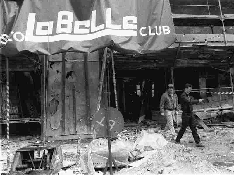 Two plainclothes U.S. military police officers walk around the scene of a bombing at the La Belle discotheque in West Berlin in this April 1986 file photo.