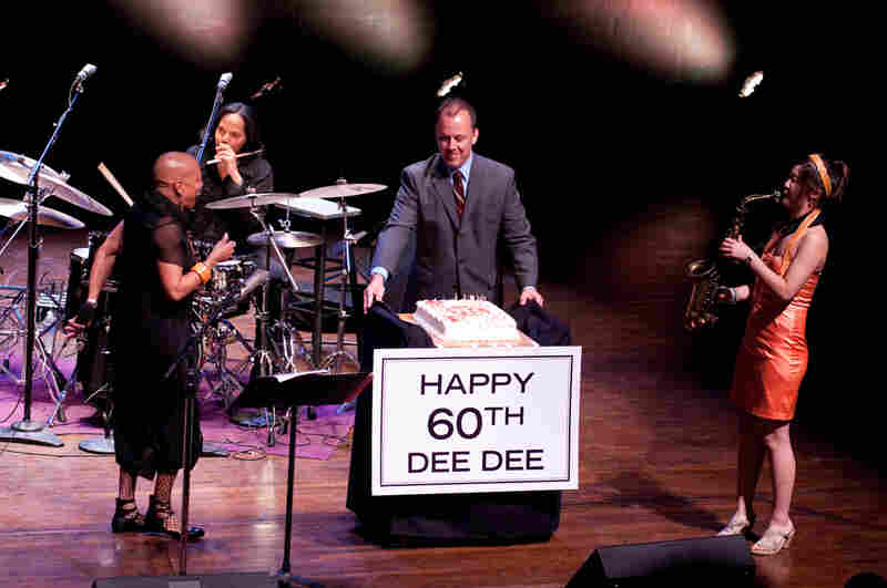 Kevin Struthers, director of jazz programming at the Kennedy Center, presents a birthday cake to Dee Dee Bridgewater, with Terri Lyne Carrington (drums) and Grace Kelly (saxophone) looking on.