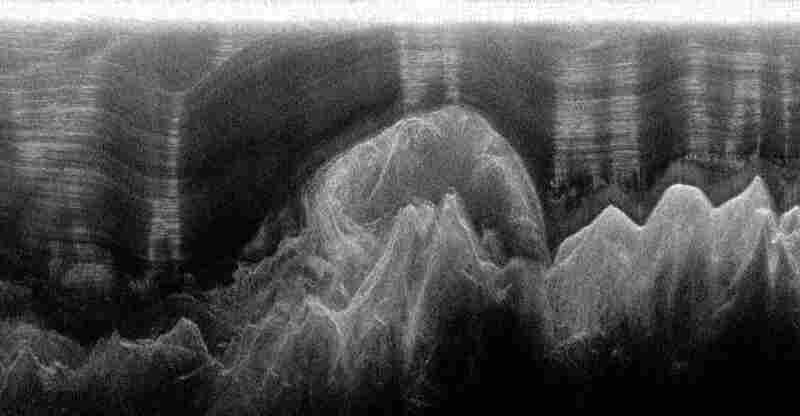 This ice-penetrating radar shows a plume of ice forming far below the ice surface. The sharp peaks at the bottom of the image are mountains, and the bulge in the center is an ice plume 1,100 meters thick. The normally flat ice layers above the mountains have been deflected 400 meters upward.