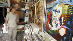 An Iraqi man walks past  paintings displayed at a gallery in the Karrada district of central Baghdad on April 13, 2010.