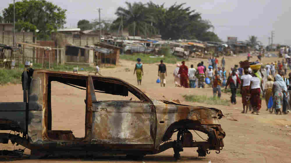 Residents walk past a burnt-out security forces vehicle in Anyama, north of Abidjan, Ivory Coast.