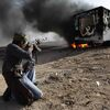 Celebrating victory in the battle for Brega, a Libyan rebel fighter takes aim at a burning vehicle that was used by troops loyal to Moammar Gadhafi.