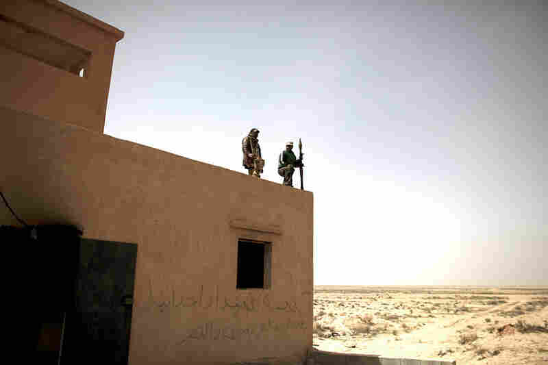 Defected Libyan soldiers stand guard outside an army base in the eastern town of Ajdabiya, Libya, on Tuesday. Eastern cities are free from government control, but fighting continues around the capital Tripoli, controlled by Libyan leader Moammar Gadhafi.