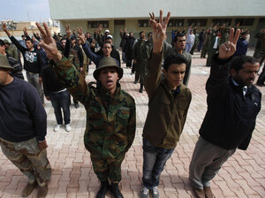 "New Libyan rebel recruits flashed the ""V"" for victory sign as they stood in formation Thursday at a training base in Benghazi."