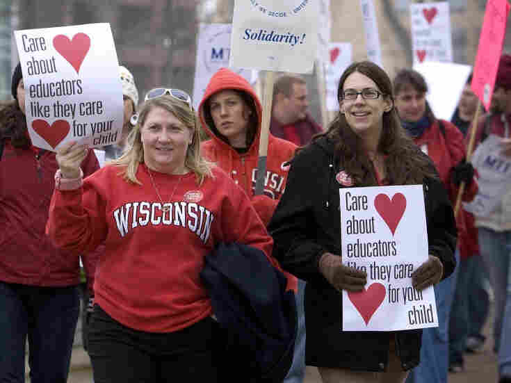 Teachers join protesters marching at the State Capitol building in Madison, Wisconsin. On Tuesday, Governor Scott Walker unveiled proposals that would cut $834 million in state school aid over two years.