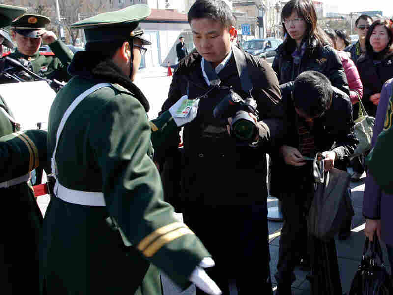 Chinese paramilitary police check  journalists' identity cards in Tiananmen Square before the opening  session of the Chinese People's Political Consultative Conference in Beijing's Great Hall of the People, China on  Thursday.