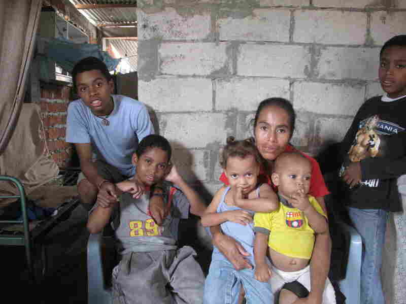 Maribel Olmedo sits in her house, surrounded by some  of her children, including Hamilton (from left), 16, Jonathan, 12, Pierina, 2, and Jose, 1. The  family struggles to make ends meet, but Olmedo says she is grateful her children are  alive.