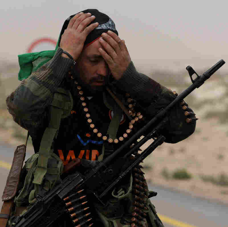 An opposition fighter readies himself before heading to the battle against pro-Gadhafi forces in Ras Lanuf.
