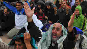 An anti-Gadhafi protester, front, reacts during Friday prayers at the court square in Benghazi, eastern Libya, Friday. Fighters loyal to Gadhafi set up checkpoints in Tripoli ahead of planned anti-government protests Friday.