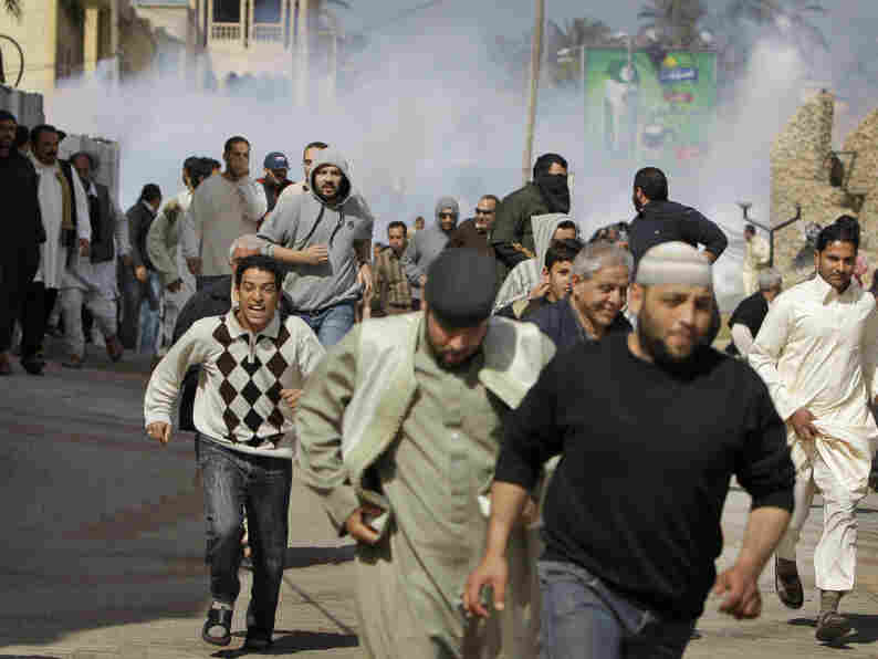 Anti-Gadhafi protesters run from tear gas fired by Libyan police in the Tajoura district of eastern Tripoli on Friday.