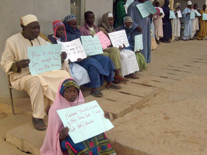 Parents and their deaf and dumb children hold placards outside a courthouse in Kano, Nigeria, in January 2008. They were waiting for the start of proceedings against Pfizer, which carried out a controversial drug trial in the country.