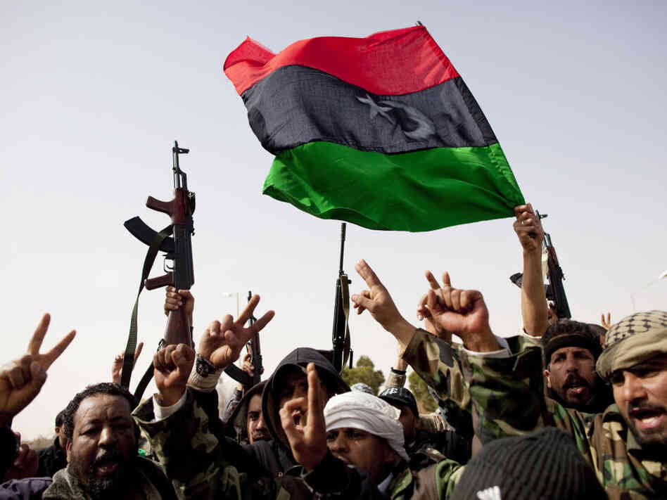 Libyan rebels fly a flag from the days before Gadhafi rule as they celebrate the capture of Ras Lanuf in eastern Libya on Saturday.