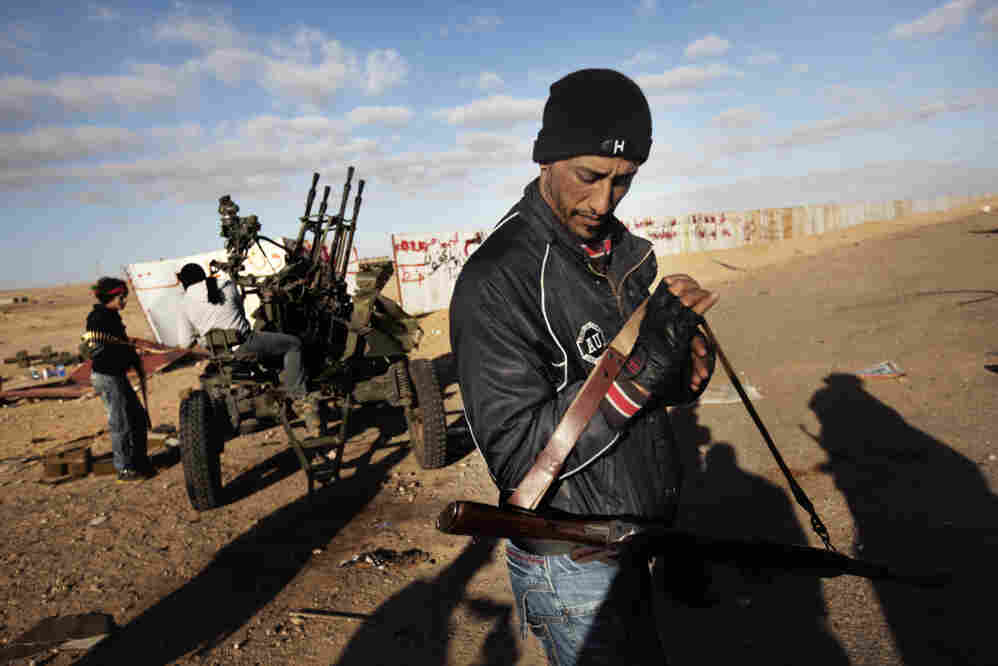 Rebel fighters prepare to defend the oil-rich town of Ras Lanuf with anti-aircraft guns on Sunday.