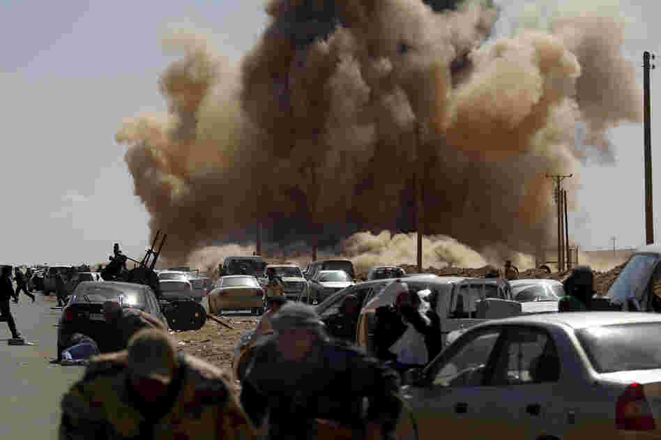 Rebel fighters take cover as a bomb dropped by an air force fighter jet explodes near a checkpoint on the outskirts of the oil town of Ras Lanuf, Libya.
