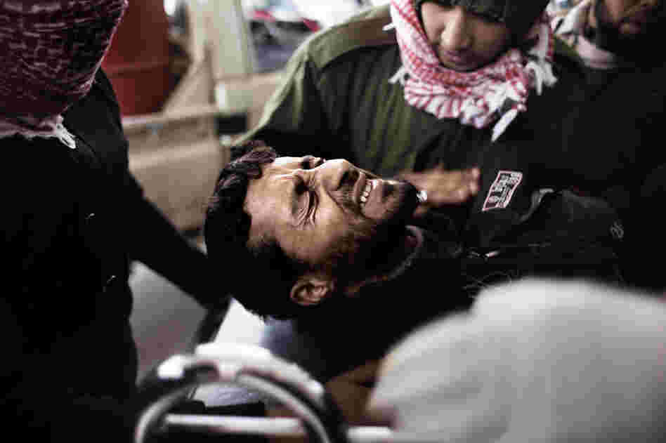 An injured rebel fighter is brought to a hospital in Ras Lanuf on Tuesday.