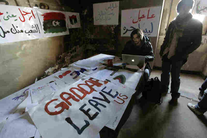 Volunteers work on anti-Gadhafi banners at the newly set-up media center in Benghazi, Libya, on Monday. Libyan activists provide technical support and documents to journalists.