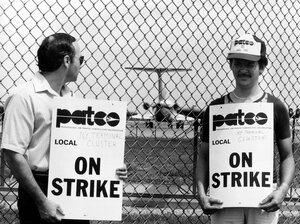 Striking air traffic controllers stand on a picket line as an airliner taxis on the runway behind them at New York's La Guardia Airport, Aug. 6, 1981.