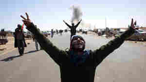 Libyan rebels on the outskirts of the oil town of Ras Lanuf flash the victory sign at a Libyan airforce fighter jet flying overhead after dropping a bomb on Monday.