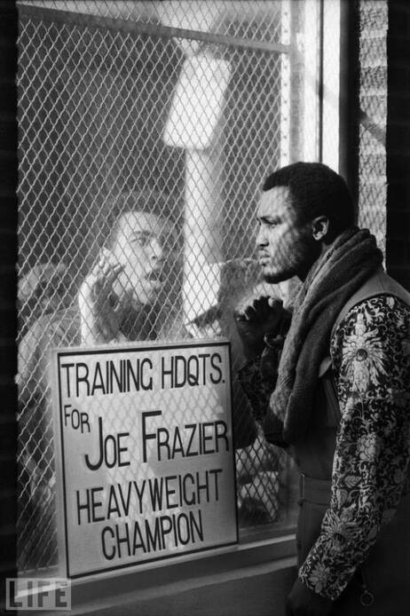 Muhammad Ali taunts Joe Frazier in  Pennsylvania at Frazier's training headquarters. Both Shearer's photos and the 1971 Life article portray the outspoken aggression between the fighters.