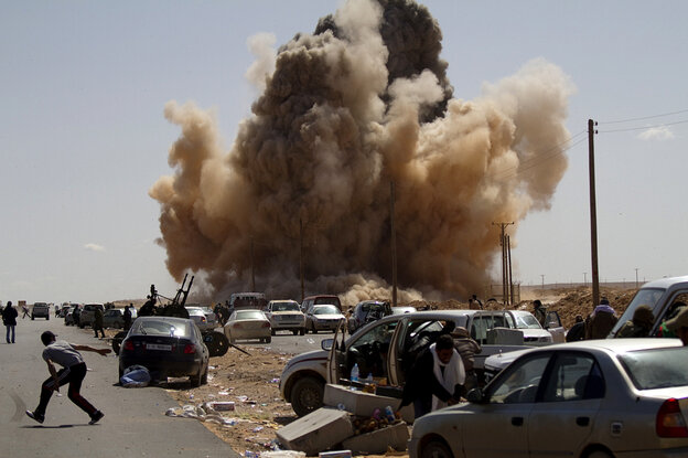 Libyan rebel fighters take cover as a bomb dropped by a fighter jet explodes near a checkpoint on the outskirts of Ras Lanuf on Monday.