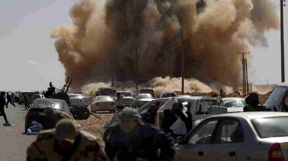 Libyan opposition fighters took cover today (March 7, 2011) as a bomb dropped by an Air Force fighter jet exploded near a checkpoint on the outskirts of the oil town of Ras Lanuf.