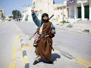 An armed resident makes a victory sign in the main square in Zawiya, Libya, on Feb. 27. Western Libya has been all but sealed off to everyone but residents and soldiers.